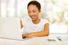 Junge afrikanische Frau, die vor Laptop sitzt Lizenzfreie Stockfotos