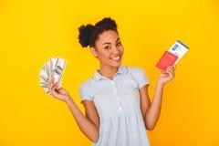 Junge afrikanische Frau lokalisiert auf Artreisendkonzept des gelben Wandstudios dem netten, das Geldpaß und -karte hält lizenzfreies stockfoto
