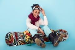 Junge afrikanische Frau lokalisiert auf dem blauen Wandstudio-Wintersport-Snowboardingkonzept, das mit Brett sitzt lizenzfreie stockfotografie