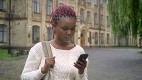 Junge afrikanische Frau mit rosa Dreadlocks schreibend am Telefon und den Rucksack, stehend im Park nahe der Universität halten,  stock video