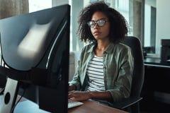 Junge afrikanische Geschäftsfrau, die auf Tischplattentastatur schreibt stockfotos