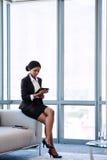 Junge afrikanische Geschäftsfrau, die den Schirm auf ihrer Tablette betrachtet Lizenzfreies Stockfoto