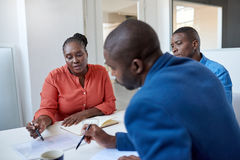 Junge afrikanische Geschäftskollegen, die Schreibarbeit in einem Büro besprechen stockbild