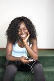 Junge Afroamerikaner-Frau, die Musik hört Stockbilder