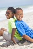 Junge Afroamerikaner-Jungen, die auf Strand sitzen Stockfoto