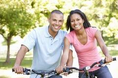 Junge Afroamerikaner-Paare, die in Park radfahren Stockfotos