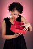 Junge Afroamerikanerfrau, die ein Geschenk öffnet Stockfoto