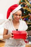 Junge Afroamerikanerfrau, die eine Geschenkbox - schwarze Menschen hält Lizenzfreie Stockbilder