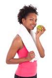 Junge Afroamerikanerfrau, die einen Apfel isst Stockfotos