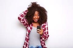 Junge Afroamerikanerfrau, die Handy mit überraschtem Ausdruck auf weißem Hintergrund betrachtet lizenzfreie stockfotos