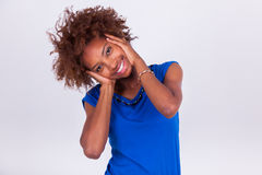 Junge Afroamerikanerfrau, die ihr krauses Afrohaar - Blac hält Stockbilder