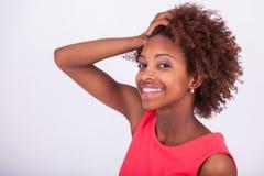 Junge Afroamerikanerfrau, die ihr krauses Afrohaar - Blac hält Stockfotografie