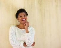Junge Afroamerikanerfrau, die mit der Hand auf Kinn denkt Lizenzfreie Stockfotos