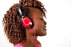 Junge Afroamerikanerfrau, die Musik hört  Lizenzfreie Stockfotos