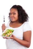 Junge Afroamerikanerfrau, die Salat isst Stockbild
