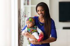 Junge Afroamerikanermutter, die mit ihrem Baby hält stockbild