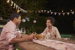 Junge Afroamerikanerpaare an einem Abendtische im Garten Stockbild