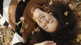 Junge afroe-amerikanisch Frau, die auf herbstlichen Blättern im sonnigen Park liegt stock video
