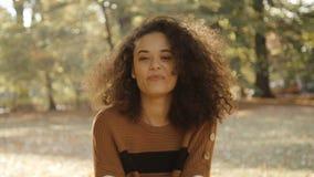 Junge afroe-amerikanisch Frau, die herbstliche Blätter oben im Park wirft stock footage