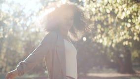 Junge afroe-amerikanisch Frau, die herbstliche Blätter oben im Park wirft stock video