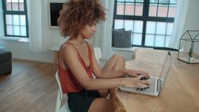 Junge afroe-amerikanisch Frau, die Laptop-Computer beim bei Tisch sitzen verwendet lizenzfreies stockfoto