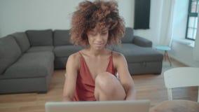 Junge afroe-amerikanisch Frau, die Laptop-Computer beim bei Tisch sitzen verwendet stock video footage