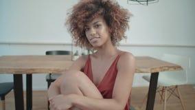 Junge afroe-amerikanisch Frau, die zu Hause durch eine Tabelle sitzt und zu einer Kamera aufwirft stock footage