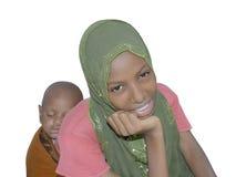 Junge Afroschönheit, die zurück ein schlafendes Baby auf ihr trägt Lizenzfreie Stockfotos