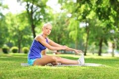 Junge aktive Frau, die auf einer excercising Matte und einem Ausdehnen sitzt Stockbilder