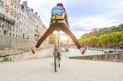 Junge aktive Frau, die Fahrrad hinuntergeht die Straße in der Stadt fährt stockfoto