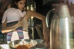 Junge aktive Mutter, die ihr Baby beim Kochen hält Lizenzfreie Stockbilder