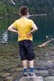 Junge alleine durch Lake Lizenzfreie Stockfotos
