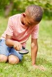 Junge als Detektiv mit Lupe stockfotografie