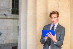 Junge amerikanische Mannlesung auf Tablet-Computer draußen Stockfotografie