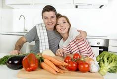 Junge amerikanische Paare, welche zu Hause die Küche vorbereitet Gemüsezusammen lächeln des salats glücklich bearbeiten Lizenzfreie Stockfotos