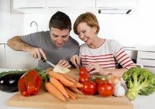 Junge amerikanische Paare, welche zu Hause die Küche vorbereitet Gemüsezusammen lächeln des salats glücklich bearbeiten Stockbilder