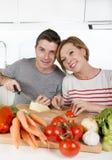 Junge amerikanische Paare, welche zu Hause die Küche vorbereitet Gemüsezusammen lächeln des salats glücklich bearbeiten Stockfoto