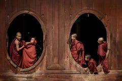 Junge Anfängermönche an Fenster hölzerner Kirche Lizenzfreies Stockbild