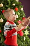 Junge anhalten anwesend vor Weihnachtsbaum Lizenzfreies Stockfoto