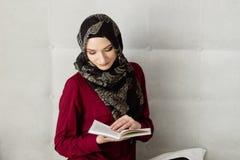 Junge arabische Frau im hijab ein Buch lesend stockbilder