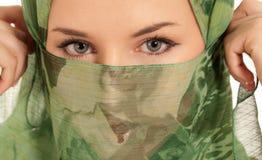 Junge arabische Frau mit dem Schleier, der die Augen getrennt zeigt Stockfotos