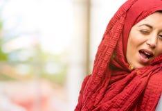 Junge arabische Frau tragendes hijab lokalisiert über natürlichem Hintergrund Lizenzfreie Stockbilder