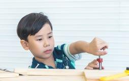 Junge arbeitet Werkzeug auf Holzarbeit in der Werkstatt aus lizenzfreie stockfotos