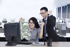 Junge Arbeitnehmer mit Geld auf Monitor Lizenzfreie Stockbilder