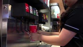 Junge Arbeitnehmerin, die kühles Brunnengetränk von der Selbstservice-Sodamaschine vorwählt stock footage