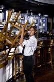 Junge Arbeitskraft, die hinunter barstools nimmt Stockfotografie