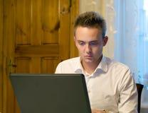 Junge Arbeitskraft mit Laptop Stockfotos
