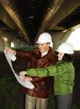Junge Architekten, die Lichtpause betrachten. stockfoto