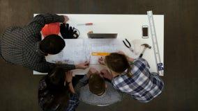 Junge Architekten, die Zeichnungsmaße mit Teiler überprüfen Lizenzfreies Stockbild