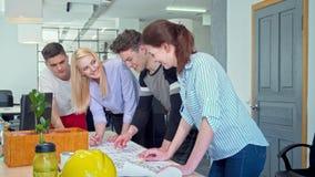 Junge Architekten, die zusammen an einem Plan im Büro arbeiten stock video footage
